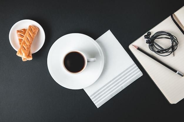Kaffeetasse mit süßigkeiten und notizbuch