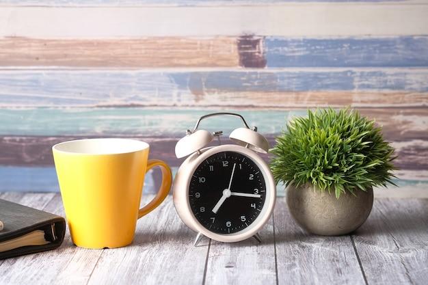 Kaffeetasse notizblock und uhr auf tisch in der nähe