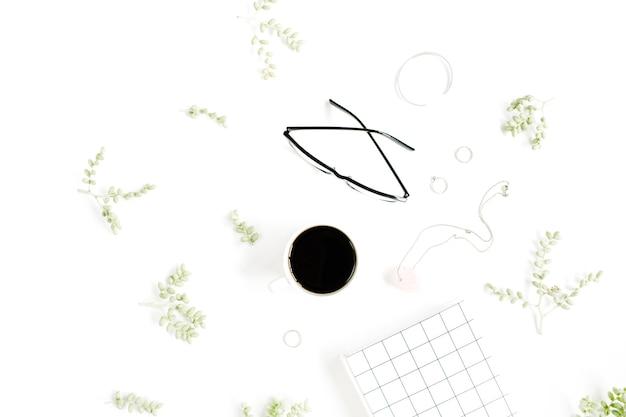 Kaffeetasse, notizbuch, gläser, grüne zweige und weibliches zubehör auf weißer oberfläche
