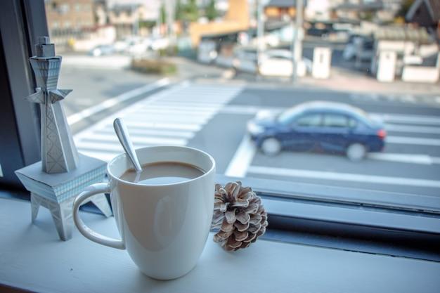 Kaffeetasse setzte an hölzerne bar am offee shopfenster
