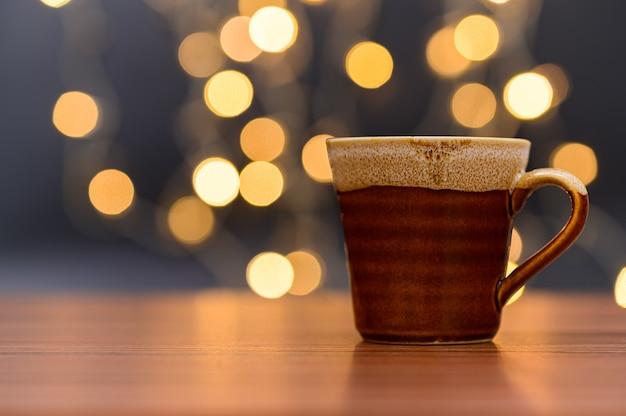 Kaffeetasse steht auf dem schreibtisch orange bokeh bodenszene