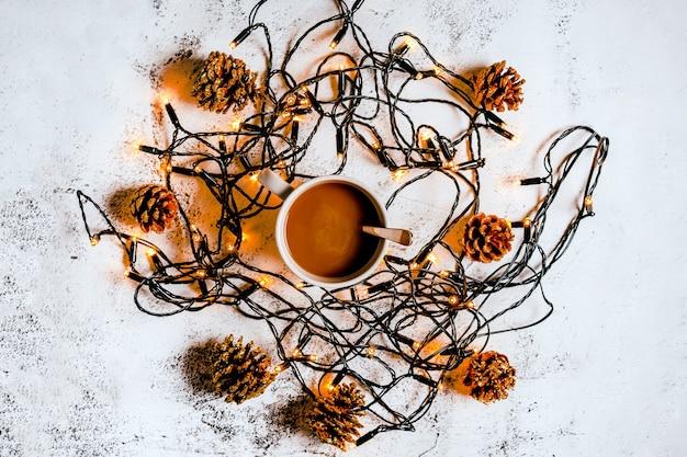 Kaffeetasse steht glühende weihnachtsgirlande auf weißem hintergrund, schönes feiertagsbanner