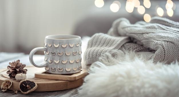 Kaffeetasse über weihnachtslichter bokeh im haus auf holztisch mit pullover an einer wand und dekorationen. weihnachtsdekoration, magische weihnachten