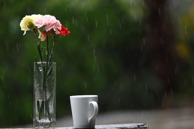 Kaffeetasse und blumenvase setzten in den garten an einem regnerischen tag ein.