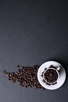 Kaffeetasse und bohnen auf altem grauem küchenbeton, steintisch. draufsicht mit copyspace
