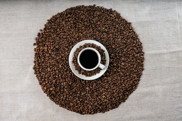 Kaffeetasse und bohnen auf altem küchentisch. ansicht von oben.