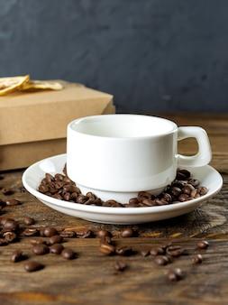 Kaffeetasse und bohnen auf altem küchentisch.