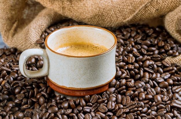 Kaffeetasse und bohnen auf einem holztisch.