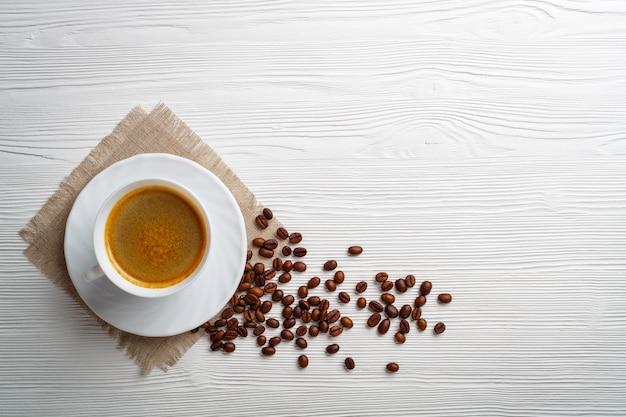 Kaffeetasse und bohnen auf einem weißen holztisch.