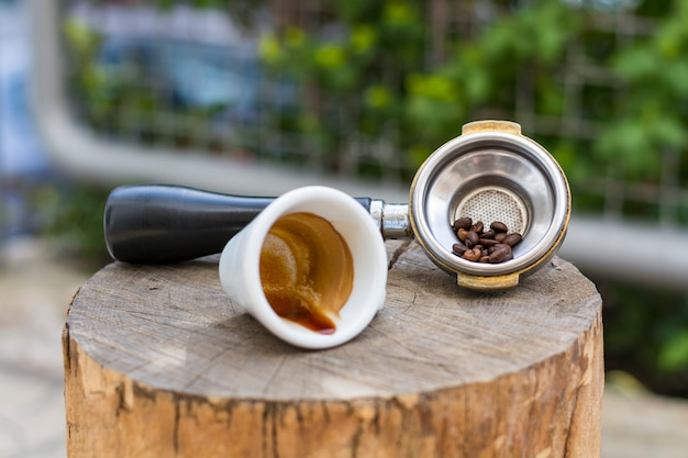 Kaffeetasse und bohnen im siebträger für espresso