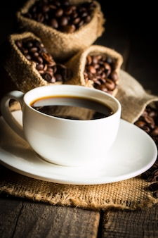 Kaffeetasse und bohnen. kaffee espresso und ein stück kuchen mit einer locke. tasse kaffee und kaffeebohnen auf tabelle.