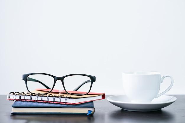 Kaffeetasse und brillen auf dem schreibtisch