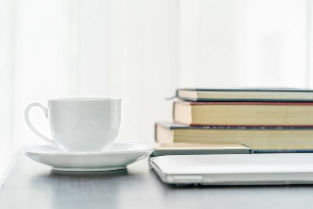 Kaffeetasse und buch auf dem tisch