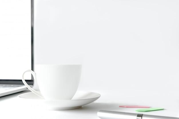 Kaffeetasse und computerdesktop auf weißer schreibtischtabelle mit einem silbernen stift und einer anmerkung