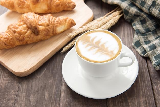 Kaffeetasse und frische gebackene hörnchen auf hölzernem hintergrund. ansicht von oben