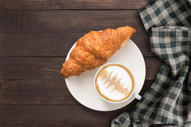 Kaffeetasse und frische gebackene hörnchen nähern sich handtuch auf hölzernem hintergrund. draufsicht, textfreiraum.