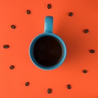 Kaffeetasse und gebratene bohnen vereinbart als ziffernblatt, draufsicht. kaffeezeit. interessantes ideenenergie und erfrischungskonzept.
