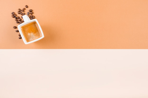 Kaffeetasse und geröstete kaffeebohnen auf doppelhintergrund