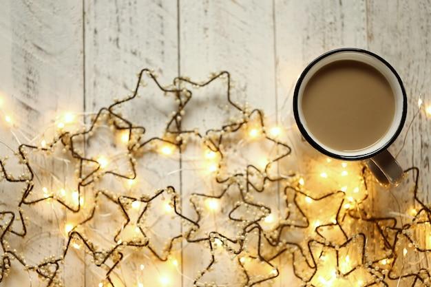 Kaffeetasse und glänzende girlande in form der sterne auf einem hellen schäbigen schicken hintergrund.