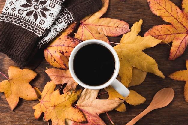 Kaffeetasse und handschuhe auf herbstlaubhintergrund