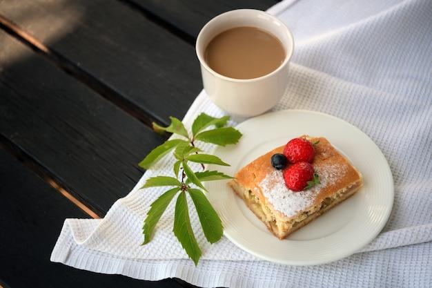 Kaffeetasse und käsekuchen auf dem tisch. cappuccino und süßer toffeekuchen. latte oder espresso mit milch