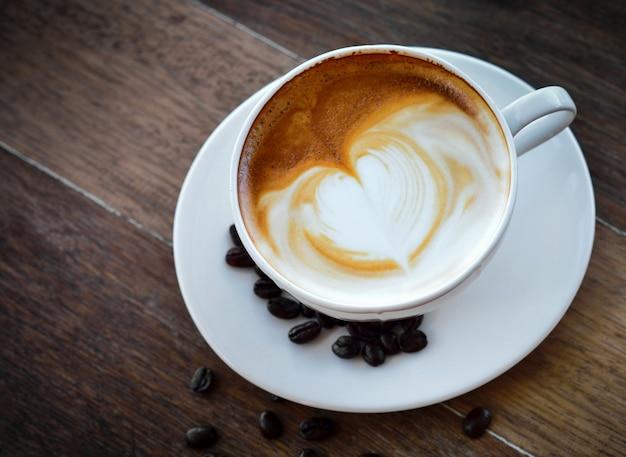 Kaffeetasse und kaffeebohnen auf altem hölzernem hintergrund