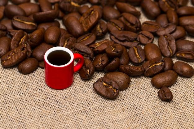 Kaffeetasse und kaffeebohnen auf dem stoffsack