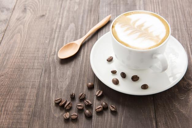 Kaffeetasse und kaffeebohnen auf hölzernem hintergrund.