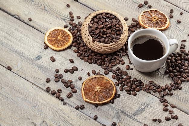 Kaffeetasse und kaffeebohnen auf hölzernem