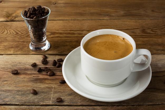 Kaffeetasse und kaffeebohnen auf rustikalem hintergrund