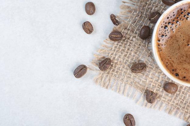 Kaffeetasse und kaffeebohnen auf sackleinen. hochwertiges foto