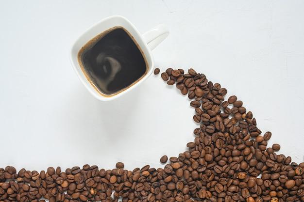 Kaffeetasse und kaffeebohnen isoliert auf weißem hintergrund