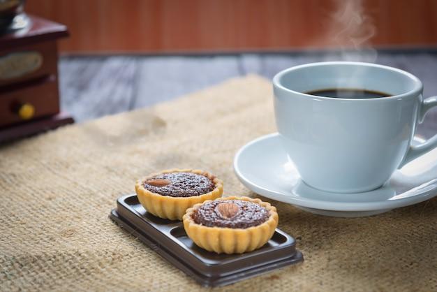 Kaffeetasse und kaffeebohnen mit schokoladenkuchentörtchen
