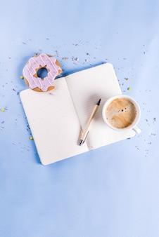 Kaffeetasse und keksdonut mit zuckerbeschichtung, mit einem notizblock