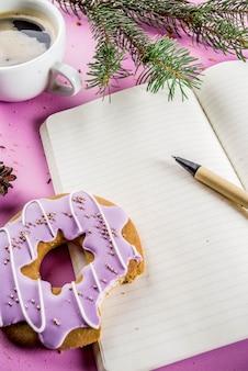 Kaffeetasse und keksdonut mit zuckerbeschichtung und notizblock