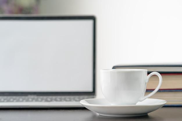 Kaffeetasse und laptop auf dem tisch