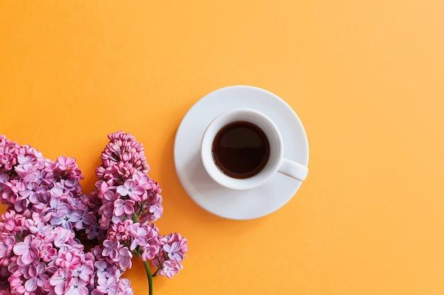 Kaffeetasse und lila blumen auf gelbem tisch.