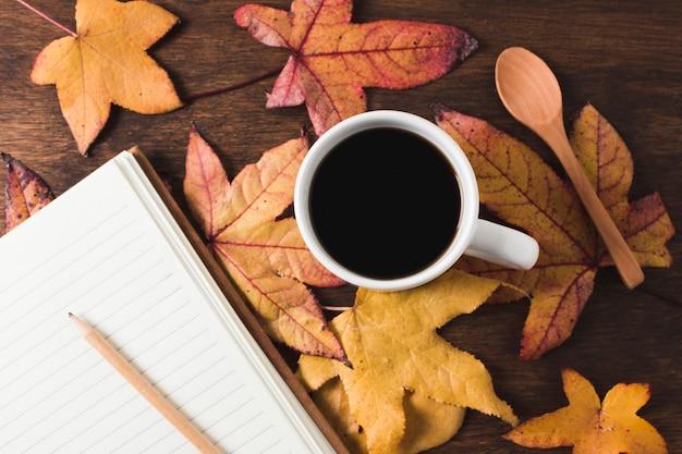 Kaffeetasse und notizbuch auf herbstlaubhintergrund