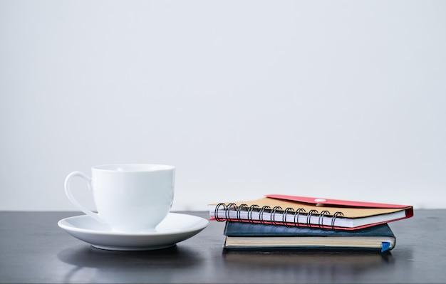 Kaffeetasse und notizbuch auf schreibtisch