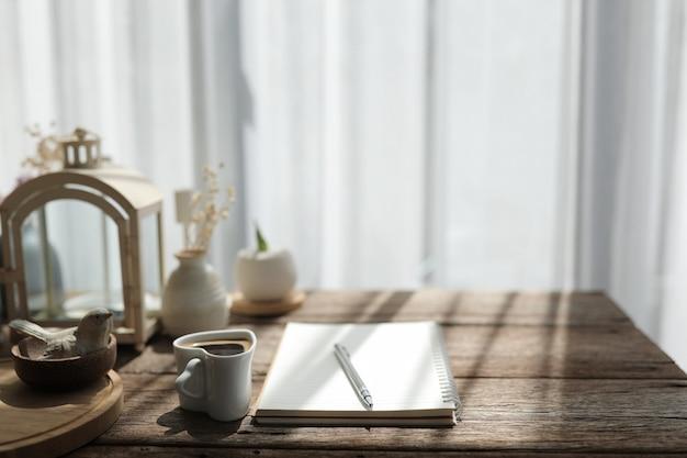 Kaffeetasse und notizbuch mit silbernem stift auf holztisch