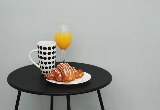 Kaffeetasse und orangensaft auf gestylten schwarzen tisch.