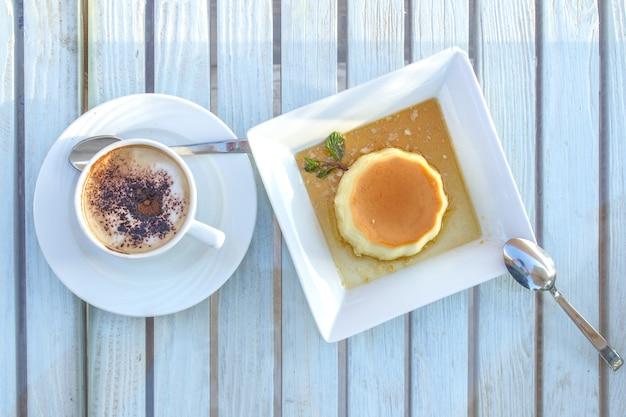 Kaffeetasse und panna cotta-nachtisch auf einem holztisch.