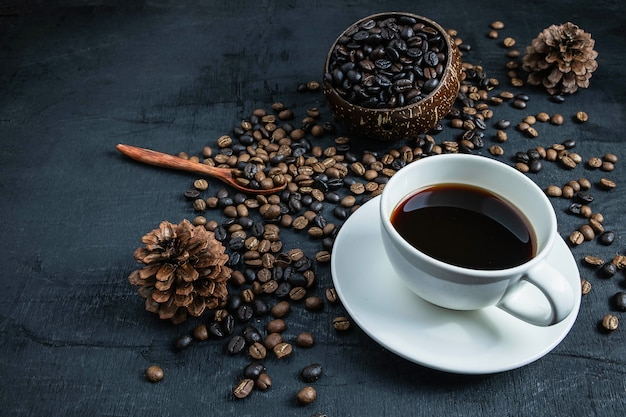 Kaffeetasse und röstkaffeebohnen auf einem schwarzen hintergrund