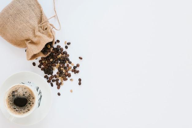 Kaffeetasse und tasche mit kaffeebohnen
