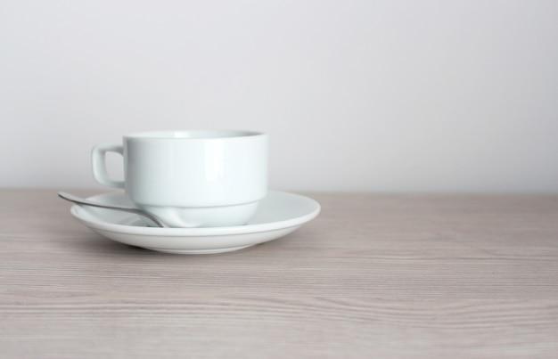 Kaffeetasse und untertasse auf holztisch