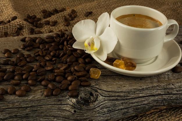 Kaffeetasse und weiße orchidee auf dem hölzernen hintergrund