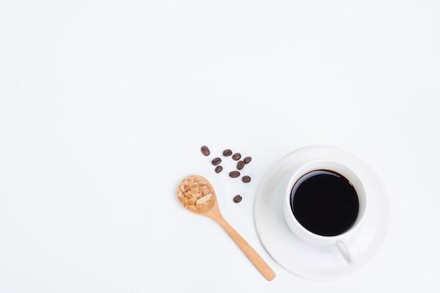 Kaffeetasse und zucker auf der kaffeebohne des hölzernen löffels lokalisiert
