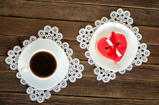 Kaffeetasse, untertasse mit rotem herzförmigen lebkuchen auf dem alten hölzernen hintergrund. ansicht von oben