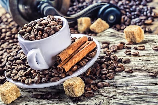 Kaffeetasse voller frischer bohnen mit braunem zucker und zimt. alles auf dem holztisch mit mahlwerk im hintergrund platziert.