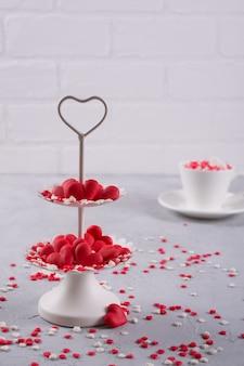 Kaffeetasse, weißes zweistufiges serviertablett voller süßer mehrfarbenstreuselzuckerherzen. liebes- und valentinstagkonzeptdekoration